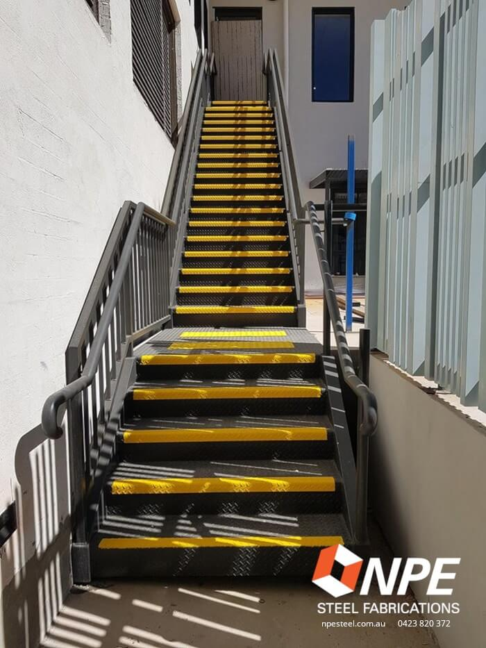 Steel stairs with handrails and tread caps.